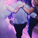 Bride and groom having fun and dancing at wedding reception